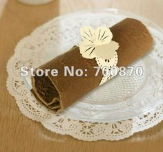 it's a laser cut napkin ring PLUS place card -- might have to have it...  NR1101-27 12pcs/pack Laser Cutting  Paper Flowers Napkin Ring Place card( silver, white,ivory and red etc) on AliExpress.com. $60.00