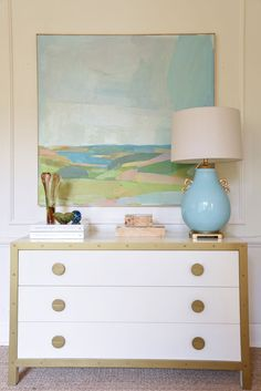 white chest with brass hardware and detailing | landscape by karen smidth | robins egg ming lamp | vintage glass and burl boxes | blue print | blueprintstore.com