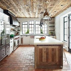 Rustic wood planked ceilings, brick floors, modern kitchen appliances, and white subway tile walls surrounding a beautiful arched window.