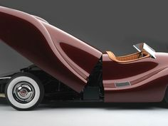 1948 Buick Streamliner. Mechanical engineer Norman E. Timbs created it himself. Custom aluminum body & steel chassis. 2 1/2 years to finish.1948 Buick V8 powered the 2200 lbs car to 120 mph. Engine is behind driver. No doors were are cut out of the body. Large one-piece rear panel opens hydraulically to reveal entire rear end of the chassis. Cost $10,000 The body was created entirely in aluminum by Emil Diedt for $8,000 The shape was formed by hand over a traditional wooden buck.