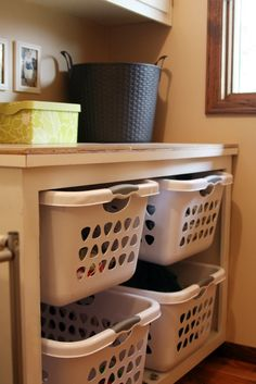 "laundry baskets under folding ledge  The ""laundry organizer"" was originally a built in cabinet with doors and I simply removed the doors so there is a shelf already in there holding up the upper laundry baskets. I just set them on the shelf."