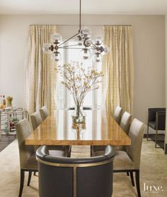 FOR THE BARREL CHAIRS.  Designer Liz Levin hung draperies higher than the window frame to emphasize the height of the dining room. The host chairs are by Arteriors; the Artistic Frame side chairs are covered with Kelly Wearstler velvet. The Modo chandelier is by Roll & Hill; the rug is by Stark.