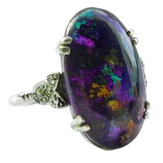 Splashing colors, ever changing, define this wonderful black opal ring set in 18K white gold with diamonds. The stone weighs 6.25 cts. Glorious in daylight and magical by candlelight, c.1920