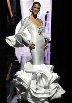 Espectacular vestido de inspiración flamenca con aires muy españoles, un vestido que esculpe el cuerpo imprimiendo fuerza y carácter a la mujer que lo lleva, realizado en seda elástica para que se adapte como un guante, con un escote generoso realzado con bordados de pedrería.