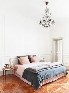A chic bedroom with pastel colored bedding and a chandelier