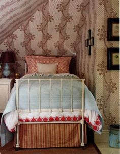 I love the white wrought iron bed in this deliciously cozy attic bedroom.  My room is just about as spacious as this.