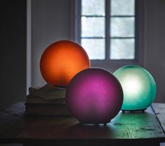 Three differently coloured round table lamps on a desk in a darkened room