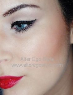 Soft defined crease, black eyeliner, flawless skin and red lips.