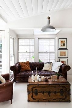 Oxblood leather couch, white    bright room. Lovely blend of the heavy masculine with airy.