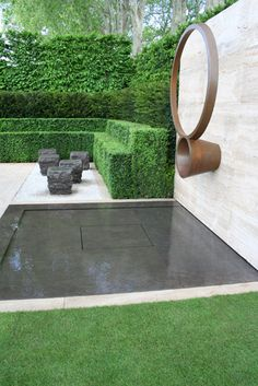Perfectly proportioned water features punctuate the design: in addition to the reflecting pool beneath the sculpture, simple pools cut into the blocks of hornbeam lead the eye out of the garden and emphasise the tranquillity of the setting.