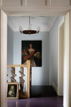 Decorating with art - London flat - Buying affordable art pieces  Two late-eighteenth-century portraits stand out against the pale blue walls of the hall, which are painted in 'Sky Blue' from Edward Bulmer's Pots of Paint. Fragments of sixteenth-century banister edge the stairs.