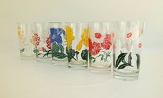 Vintage 1950s set of 6 swanky swigs glass tumblers. This set of swanky swig glasses each feature a different fun bright flower design wrapping around each glass. #swankyswigs #retro #vintage