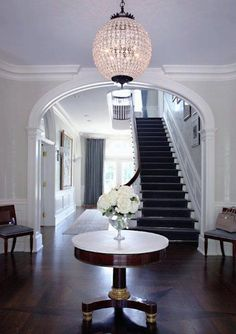 SB Long Interiors - entrances/foyers - crown molding, foyer table, pedestal foyer table, marble topped pedestal table, entry table | Another chandelier worthy of note @sblonginteriors http://homeandecoration.com/s-b-long-interiors-talent-design/