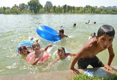 Romanian children play in the water of a lake on July 15, 2012.