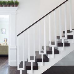 Cool modern stairs yet traditional trim detailing etc. like the mix