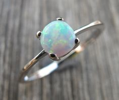 Gorgeous Sterling Silver Ring in round shaped Opal. It is absolutely mesmerizing with revealing rainbow hues that are so lovely to stare at! Wrapped in a box ready for gift giving.(r33)  Opal measure 5mm  Matching Stud Earring: https://www.etsy.com/listing/214922634/christmas-sale-white-opal-studs-post?ref=shop_home_active_3  Matching Necklace: https://www.etsy.com/listing/214915400/christmas-sale-white-opal-necklace-opal?ref=shop_home_active_2&ga_search_query=opal%2Bnecklace  Also available…