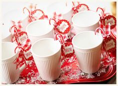 Embellish simple mugs with candy cane and ribbon--guests can keep them as a favor after the party! #partycrafters #winter