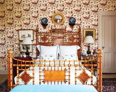 The walls of a guest room are covered in a Georges Le Manach cotton, and the 19th-century bamboo bed is dressed with Matouk linens.