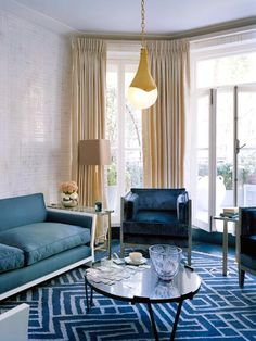 The design of the geometric blue rug echoes the strong angles of the armchairs and sofa in this living room.