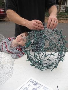 Make a hanging light ball by wrapping twinkle lights around a ball made of chicken wire.