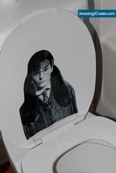 Picture of Moaning Myrtle printed in black & white on transparency paper and placed on toilet in guest bathroom.