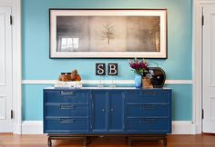 I like the darker blue dresser against the lighter blue wall. Maybe use red spicket handles for knobs.