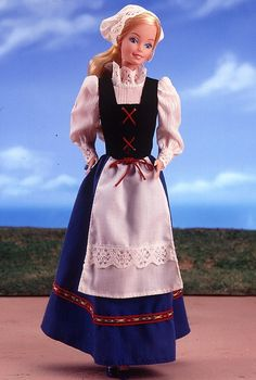 "Swedish Barbie doll wears a traditional blue jumper dress with red trim called a ""bunad."" Over her dress is a crisp white apron accented with white lace, and tied with red ribbon. Her white blouse features beautiful pouffed sleeves and a ruffled collar. She has a matching white bonnet over her blond hair."