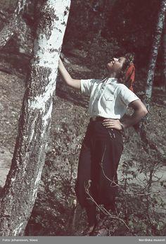 1941. Kvinna med ljus skjorta, mörka byxor och röd toppluva lutar mot en björk. Fotograf: Gunnar Lundh