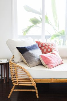 Rattan and bright coloured cushions in the sitting room in the relaxed and light-filled L.A home of Victoria from SF Girl By Bay. Laure Joliet.