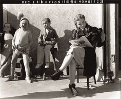 Judy Garland (reading Life magazine) and some munchkin actors between takes on the set of The Wizard of Oz (directed by Victor Fleming and George Cukor), December 23, 1938