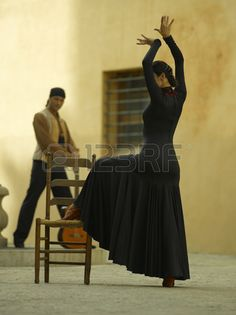 Side profile of a female dancer dancing with a young man holding a guitar in the background photo