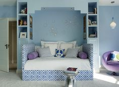 Blue and purple girl's bedroom features blue built-in bookcases flanking a built-in alcove with an ...