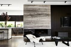 The designer combined richly textured travertine stone with dark timber and elegant blackened steel to create visual interest.
