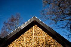 stacked wood behind glass = modern take on cordwood walls