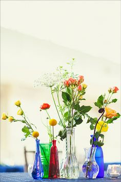 A grouping of clear and/or white vases with pink and white flowers