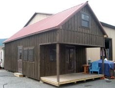 Pine Creek Structures bargain corner mill hall board n batten wood metal roof two story peak cabin