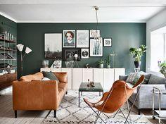 I vardagsrummet har väggarna målats i en behaglig grön kulör ur kollektionen Balance från Jotun. Den sköna gröna nyansen sätter en trivsam stämning samtidigt som den lyfter både möbler, tavlor och inredningsaccessoarer. Sofforna är från Ikea med nya ben från Prettypegs. Även skåpen Ivar längs väggen kommer från Ikea och har betsats i vitt. String-hyllorna är nyproducerade i valnöt och den trearmade lampan är köpt på Myrorna. Soffbord från Bolia, matta från Ellos och fladdermusfåtöljen ...