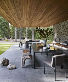 Martis Camp/Lake Tahoe outdoor living room featuring marble table and teak benches atop sandstone tiles: Jamie Bush Co. and Cynthia Wang