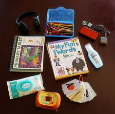 A pencil box full of coloring supplies, which pair up with the drawing and writing pads shown in the bottom right corner.    Alphabet flash cards.    Handheld video game device, games and charger.    Camera.    Hand sanitizer {alcohol free}.    Baby wipes for quick clean ups.    Reading material/books.    Oh, and headphones for the car movie player {pictured way above}