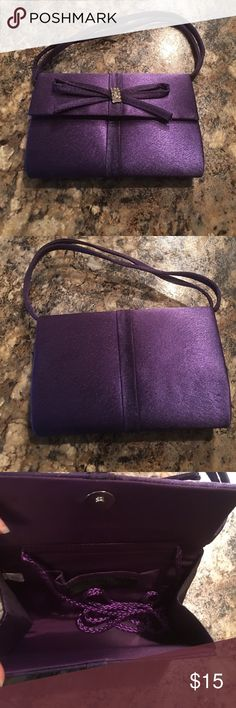 Purple clutch Clutch is purple with a bow that's has a diamond studded center. Clutch is small. Does have a two strand handle to carry on your wrist and a long handle in the inside to wear on your shoulder. Purse only been worn once in good condition Jessica McClintock Bags Mini Bags