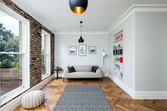 Small living room with brick wall and Tom Dixon pendants [From: David Butler Photography]