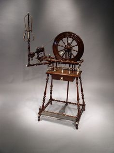 """Probably York, England Circa 1800.     An exceptional example of a late eighteenth century English Spinning Wheel, the supports and rails finely turned in rosewood, having a turned rosewood wheel, and with a rosewood work platform having a suspended frieze drawer beneath with an ivory ring handle, the gallery above with turned ivory uprights and applied ivory roundels to the intersections, various ivory roundels and finials throughout. Measurements: 41"""" High; 24"""" Wide; 17"""" Deep"""