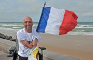 French amputee and swimmer Philippe Croizon posing with a French flag in Wissant, northern France after he succeeded on September 18 his attempt to swim the English Channel, a challenge he has been preparing for two years. A Frenchman who gained fame for swimming the English Channel with no arms or legs has set himself a new challenge: to cross five continents in waters marked by sharks, poisonous jelly fish, icy currents, & cargo ships.