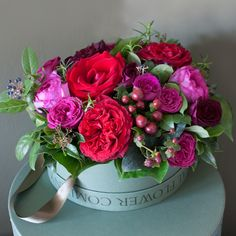 This red festive hat box arrangement has a mixture of luxury scented Lady Killer, Deep Secret, Yves Piaget roses with the beautifully blowsy Red Elegance roses which are exclusively grown on our farm in Kenya. We have mixed these beautiful roses with Red Hypericum berries in this deluxe arrangement with aromatic herbs and seasonal winter foliage, all grown on our English Farm. The hat box will make a lovely keep sake after the flowers have faded.