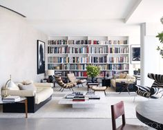At Home in the Sky - The living area of Andrew Rosen and Jenny Dyer's Manhattan apartment, which Dyer designed. The 1970s leather Pace sofas have lacquered bases; the shelving is custom made, and the photograph at right is by Jack Pierson.
