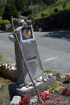 Waymarker and discarded walking boots, staff and gourd. Pilgrim motifs in San Miguel de Valga, Galicia, Spain. Final 2 days walking the Portuguese Way of St. James from Caldas de Reis to Santiago de Compostela Cathedral. Highs, lows and more on the Camino Português