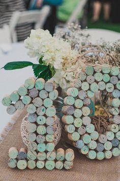 Seafoam painted wine cork table numbers and string balls on burlap table runner.