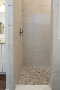 Pebble shower floor Sleek yet soft gray tiles carve out a gorgeous walk-in shower in this transitional bathroom. Pebble tile floors in gray tones coordinate with the walls while adding striking interest underfoot. Pebble Shower Floor, Gray Shower Tile, Bathroom Floor Tiles, Gray Tiles, Bathroom Grey, Master Bathroom, Shower Bathroom, Room Tiles, Wall Tiles
