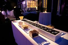 To create an interactive s'mores station, fill a five-foot-long box with black river rock to simulate charcoal and embed Sterno cans in the rocks.