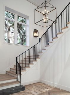 Chic foyer features a staircase boasting an iron railing and medium stained wood treads illuminated by a glass and iron lantern.